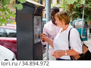Polite intelligent African man helping middle aged woman to buy ticket in parking meter on summer city street. Стоковое фото, фотограф Яков Филимонов / Фотобанк Лори