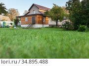 Empty well-groomed lawn with green grass is in front of modern cottage, backyard. Стоковое фото, фотограф Кекяляйнен Андрей / Фотобанк Лори