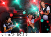 Smiling young friends playing laser tag game with colored laser. Стоковое фото, фотограф Яков Филимонов / Фотобанк Лори