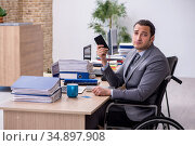 Young male enployee in wheel-chair at workplace. Стоковое фото, фотограф Elnur / Фотобанк Лори
