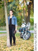 Attractive Caucasian woman biker with a motorcycle is in a park or forest at autumn season, full length portrait. Стоковое фото, фотограф Кекяляйнен Андрей / Фотобанк Лори
