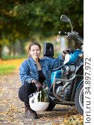 Female motorcycle rider with white crash helmet in hand sitting near her blue bike. Стоковое фото, фотограф Кекяляйнен Андрей / Фотобанк Лори