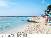 Ayia Napa, Cyprus-circa Sep, 2010: White sand and turquoise sea water are on the Nissi beach. It is a popular beach in the resort of Ayia Napa. The beach have small islet of Nissi. Редакционное фото, фотограф Кекяляйнен Андрей / Фотобанк Лори