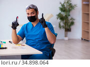Young male biochemist testing blood samples in pandemic concept. Стоковое фото, фотограф Elnur / Фотобанк Лори