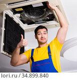 Repairman repairing ceiling air conditioning unit. Стоковое фото, фотограф Elnur / Фотобанк Лори