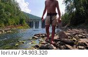Water dam in the forest - a young man in shorts walking on rocks. Стоковое видео, видеограф Константин Шишкин / Фотобанк Лори