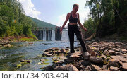 Young woman on vacation - walking on rocks near the streaming water - a waterfall dam on a background. Стоковое видео, видеограф Константин Шишкин / Фотобанк Лори