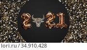 Happy New year 2021 celebration. Bright gold balloons figures, New Year Balloons with glitter stars on dark background. Christmas celebration. Gold foil balloons With symbol of the year of the bull. Стоковое фото, фотограф Сергей Тимофеев / Фотобанк Лори