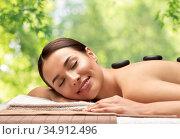 smiling woman having hot stone massage at spa. Стоковое фото, фотограф Syda Productions / Фотобанк Лори