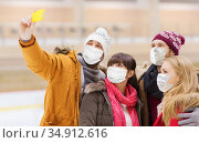 friends in masks taking selfie on skating rink. Стоковое фото, фотограф Syda Productions / Фотобанк Лори