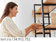 woman placing aroma reed diffuser to shelf home. Стоковое фото, фотограф Syda Productions / Фотобанк Лори