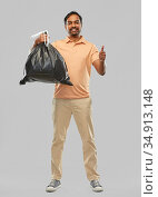 happy indian man with trash bag showing thumbs up. Стоковое фото, фотограф Syda Productions / Фотобанк Лори