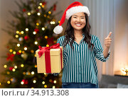 asian woman with christmas gift showing thumbs up. Стоковое фото, фотограф Syda Productions / Фотобанк Лори