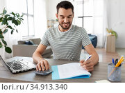 man with files and calculator works at home office. Стоковое фото, фотограф Syda Productions / Фотобанк Лори
