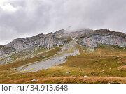 Beautiful autumn mountain landscape with rocky peak in the clouds. Стоковое фото, фотограф Евгений Харитонов / Фотобанк Лори