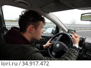 Gruenheide, Germany, young man shows his middle finger while driving. Редакционное фото, агентство Caro Photoagency / Фотобанк Лори