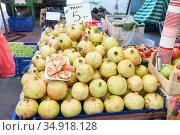 Pomegranates are stacked in pile on Turkish farmer market. Fruit and vegetable marketplace is in the Alanya, Turkey. Стоковое фото, фотограф Кекяляйнен Андрей / Фотобанк Лори