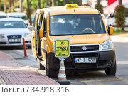 Yellow cab stands on the special parking place for taxi cars. Van with opened doors is waiting for passengers. Taxi service is in Alanya city. Turkey. Редакционное фото, фотограф Кекяляйнен Андрей / Фотобанк Лори
