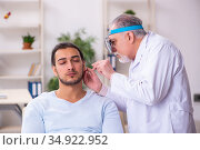 Young sick man visiting old doctor otolaryngologist. Стоковое фото, фотограф Elnur / Фотобанк Лори