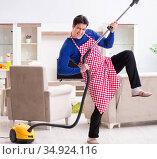 Young man vacuum cleaning his apartment. Стоковое фото, фотограф Elnur / Фотобанк Лори