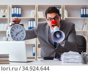 Clown businessman angry in the office with a megaphone. Стоковое фото, фотограф Elnur / Фотобанк Лори