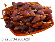 Fresh dates on wooden plate, healthy snack. Стоковое фото, фотограф Яков Филимонов / Фотобанк Лори