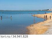 Люди мажутся лечебной грязью на Сакском озере, Крым. Редакционное фото, фотограф Николай Мухорин / Фотобанк Лори
