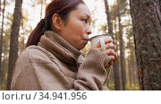 asian young woman drinking hot tea in forest. Стоковое видео, видеограф Syda Productions / Фотобанк Лори