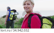 Portrait of senior hiker woman with backpack and trekking poles smiling while standing on the grass . Стоковое видео, агентство Wavebreak Media / Фотобанк Лори