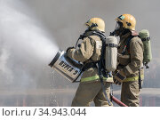 Firefighters extinguishes fire from fire hose, using fire-fighting water-foam barrel with air-mechanical foam (2019 год). Редакционное фото, фотограф А. А. Пирагис / Фотобанк Лори