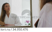 Woman in bathrobe brushing her hair while looking in the mirror. Стоковое видео, агентство Wavebreak Media / Фотобанк Лори