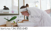 Woman in bathrobe washing her face in the sink. Стоковое видео, агентство Wavebreak Media / Фотобанк Лори