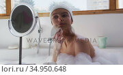 Woman cleansing her face with cotton pad while sitting in bathtub. Стоковое видео, агентство Wavebreak Media / Фотобанк Лори