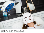 Woman receiving face light therapy in LED mask. Стоковое фото, фотограф Яков Филимонов / Фотобанк Лори