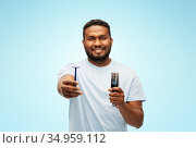smiling african man with razor blade and trimmer. Стоковое фото, фотограф Syda Productions / Фотобанк Лори