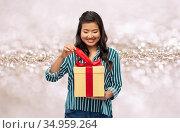 happy asian woman opening gift box. Стоковое фото, фотограф Syda Productions / Фотобанк Лори