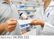 pharmacist and customer with medicine at pharmacy. Стоковое фото, фотограф Syda Productions / Фотобанк Лори