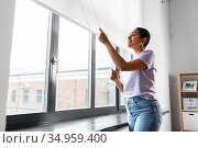 woman opening window roller blinds. Стоковое фото, фотограф Syda Productions / Фотобанк Лори