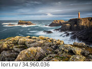 Butt of Lewis lighthouse viewed across rocky cliffs and sea, in stormy light. Isle of Lewis, Outer Hebrides, Scotland, UK. November 2016. Стоковое фото, фотограф Guy Edwardes / Nature Picture Library / Фотобанк Лори