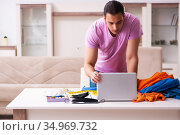 Young male tailor receiving order via Internet during pandemic. Стоковое фото, фотограф Elnur / Фотобанк Лори