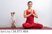 Caucasian woman in red jumpsuit sits in lotus position next to the dog. Yoga with a pet. Стоковое фото, фотограф Михаил Решетников / Фотобанк Лори
