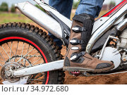 Close up view at rider's motocross boot standing on peg of dirt motorcycle. Safety apparel for riding. Стоковое фото, фотограф Кекяляйнен Андрей / Фотобанк Лори