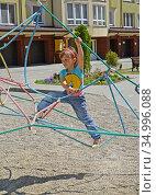 Девочка забирается на канатную  пирамиду. Детская площадка. Стоковое фото, фотограф Ирина Борсученко / Фотобанк Лори