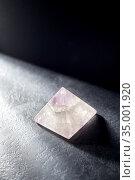 quartz crystal pyramid on slate stone in darkness. Стоковое фото, фотограф Syda Productions / Фотобанк Лори