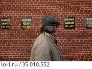 Мужчина смотрит на таблички с именами государственных деятелей СССР в Некрополе у Кремлёвской стены на Красной площади в центре города Москвы, Россия. Редакционное фото, фотограф Николай Винокуров / Фотобанк Лори