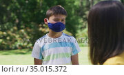 Portrait of caucasian brother and sister wearing face mask standing in the garden. Стоковое видео, агентство Wavebreak Media / Фотобанк Лори