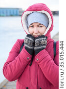 Portrait of an adult Caucasian woman dressed warm red jacket with hood on her head and knit mittens standing on quay of frozen lake. Стоковое фото, фотограф Кекяляйнен Андрей / Фотобанк Лори
