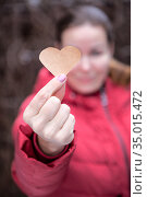 Attractive Caucasian woman wearing warm red jacket is outstretched hand wit paper heart. Стоковое фото, фотограф Кекяляйнен Андрей / Фотобанк Лори