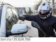 Motorcyclist beat side-view mirror of car with a fist, conflict is on the road. Стоковое фото, фотограф Кекяляйнен Андрей / Фотобанк Лори