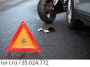 Emergency warning triangle positioned on asphalt road due accident with a motorcycle and a car. Стоковое фото, фотограф Кекяляйнен Андрей / Фотобанк Лори